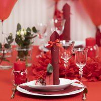 Decoraciones para mesa en rojo con flores de papel, globos, una servilleta doblada como una torre y tarjetas de lugar.