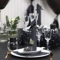 Decoraciones para mesa en negro con flores de papel, globos, una servilleta enrollada como una torre y tarjetas de lugar.