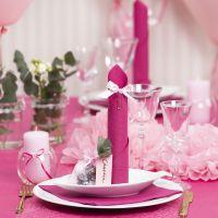 Decoraciones para mesa en rojo claro con flores de papel, globos, una servilleta doblada como una torre y tarjetas de lugar.
