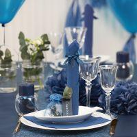 Decoraciones para mesa en azul oscuro con flores de papel, globos, una servilleta doblada como una torre y tarjetas de lugar.
