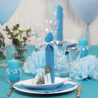 Decoraciones para la mesa en azul claro con flores de papel, globos, servilleta doblada como una torre y tarjetas de lugar.