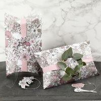Cajas almohadas decoradas con cinta rosa, un aro de metal y recortables de flor.
