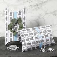 Cajas almohadas decoradas con cinta azul, un aro de metal y decoraciones de recortables marítimos.