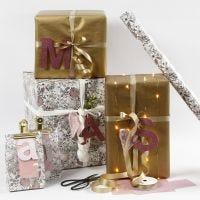 Papel de regalo rosa y dorado con letras de papel de diseño.