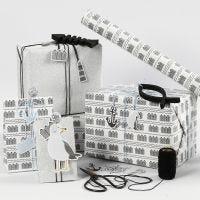 Envoltorio de regalo negro, blanco y plata brillante con tarjetas, pez de madera y clips para papel de metal efecto shaker.