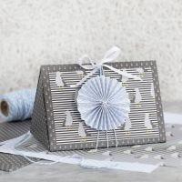 Una caja de regalo azul oscura decorada con una roseta azul y papel de diseño.