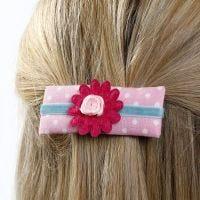 Un pasador hecho de cartulina decorada con tela, cinta y flores de tela