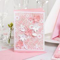 Una invitación con cartulina de encaje y flores troqueladas con un efecto 3D