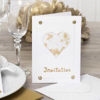 Una invitación decorada con un corazón de papel vellum, purpurina, pedrería y papel Deco Foil.