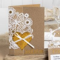 Una invitación decorada con encaje de cartulina, corazón de Deco Foil y pedrería.