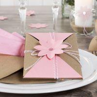 Una invitación envuelta y cerrada con cordón de algodón y una flor troquelada.