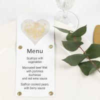 Una carta de menú decorada con un corazón de papel vellum, purpurina y pedrería