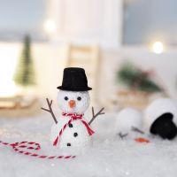 El elfo construye un muñeco de nieve delante de su puerta principal