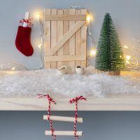 La puerta del Elfo de palos de polo con una escalera de cuerda y un calcetín de Navidad como buzón.