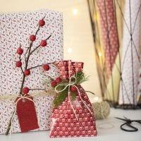 Envoltorio de regalos navideños con una ramita y bayas artificiales.