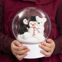 Un adorno transparente con soporte y un muñeco de nieve, un pingüino y un oso polar en su interior