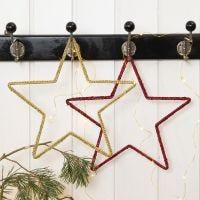 Una estrella de Navidad tejida a ganchillo en un marco metálico en forma de estrella
