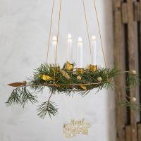 Una corona de Adviento para colgar con soportes para vela de alambre de bonsai y decoraciones de papel imitación cuero.
