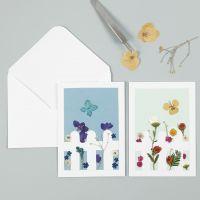 Una tarjeta de felicitación con flores secas tras una valla de madera