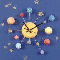 Un reloj de pared decorado con planetas de Silk Clay, pegatinas de estrellas y alambre para bonsai.
