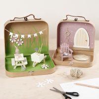 Pequeñas maletas transformadas en un mundo jardín con pintura, muebles en miniatura y accesorios