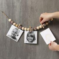 Fotos en un trozo de hilo natural con cuentas de madera, clavijas y lentejuelas