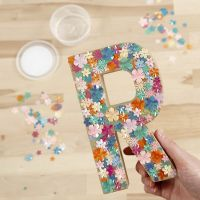 Una letra de papel maché decorada con lentejuelas y base adhesiva
