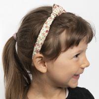 Una cinta para el pelo decorada con un nudo de tela.