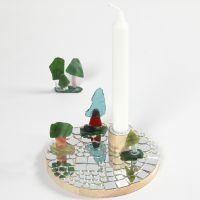 Un candelabro sobre una base de madera con mosaicos