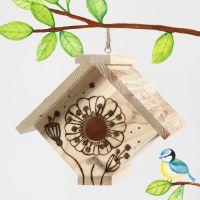 Una casita para pájaro decorada con una herramienta de pirograbado.