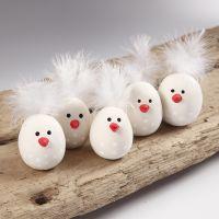 Pollitos de Pascua hechos de arcilla autoendurecible con una pluma para la cola.