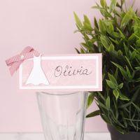 Una tarjeta de lugar para una fiesta de confirmación decorada con un vestido y un lazo.