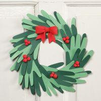Una corona de navidad hecha de manos recortadas con decoraciones de Silk Clay