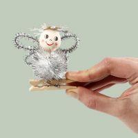 Un ángel hecho de un pompón y limpiadores de tuberías en una clavija de madera