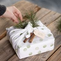 Envoltorio de regalo con un paño de cocina decorado con un diseño estampado