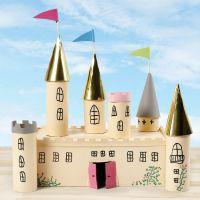 Un castillo de cuento de hadas de una caja de cartón y tubos de cartón decorados con pintura artesanal