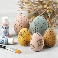 Huevos de madera manchados decorados con una herramienta pirográfica.