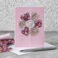 Una tarjeta de felicitación con un diseño de flor de tela cosida