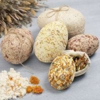 Two-part papier-mâché Easter eggs covered with pulp and dried flowers
